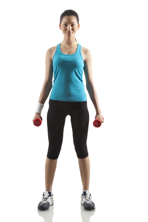 Portrait of young woman exercising with dumbbells isolated over white background