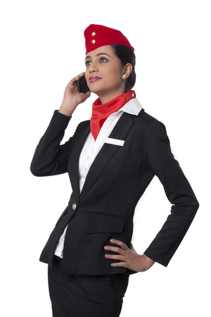Young airhostess using cell phone while looking up isolated over white background