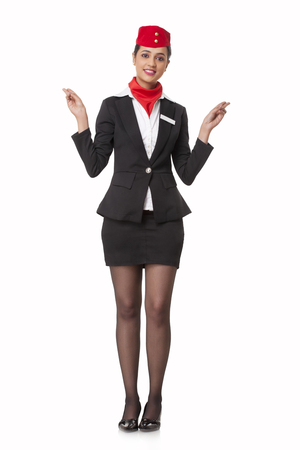 Portrait of young stewardess indicating exits isolated over white background