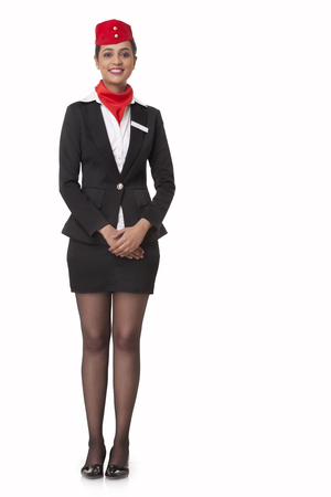 welldressed: Full length portrait of young airhostess standing over white background