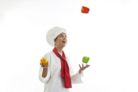 Young female chef juggling bell peppers isolated over white background Stock Photo