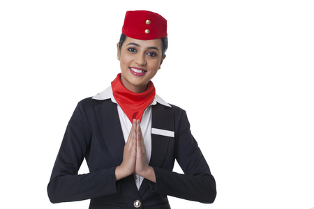 Portrait of young airhostess greeting Namaste isolated over white background