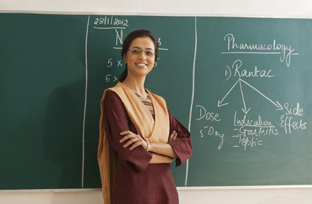 kurta: Portrait of young female teacher in traditional clothing standing with arms crossed against chalkboard
