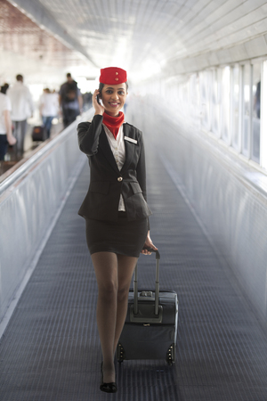 Young air hostess with luggage bag using cell phone while on call