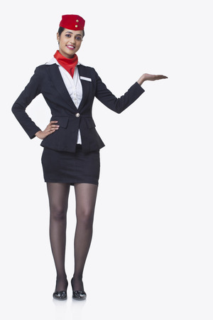 Portrait of an airhostess holding invisible product isolated over white background