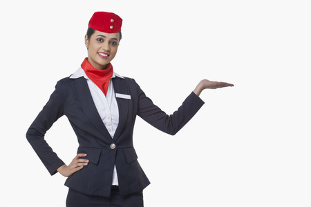 Portrait of young airhostess holding invisible product isolated over white background