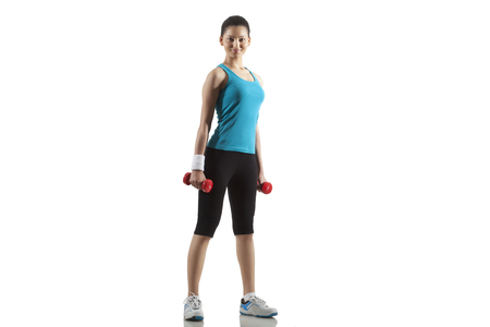 Portrait of fit young woman exercising with dumbbells isolated over white background Stock Photo