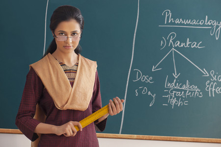Portrait of young female teacher with attitude holding ruler against chalkboard