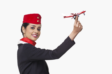 Portrait of an airhostess holding toy airplane isolated over white background