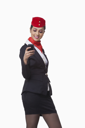 Happy young airhostess text messaging on cell phone isolated over white background