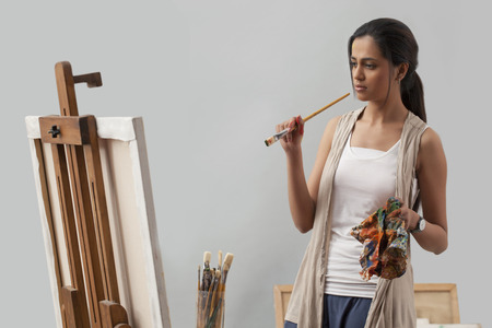 Thoughtful young female artist looking at painting
