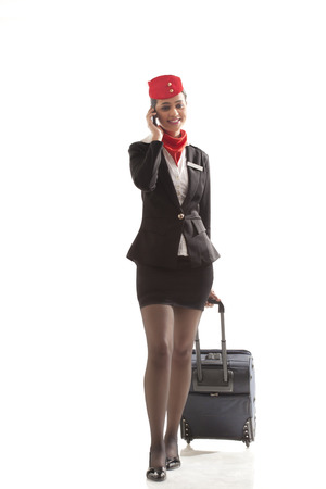 An airhostess on call while pulling luggage bag isolated over white background Stock Photo