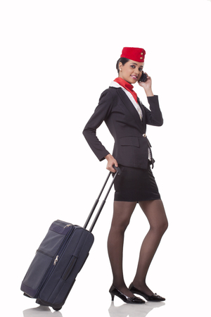 Portrait of an airhostess on call while holding luggage bags handle isolated over white background