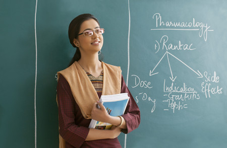 Young female teacher contemplating while leaning on chalkboard Stock Photo