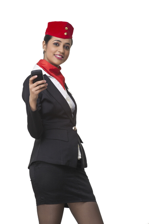 Portrait of happy young airhostess text messaging on cell phone isolated over white background Stock Photo