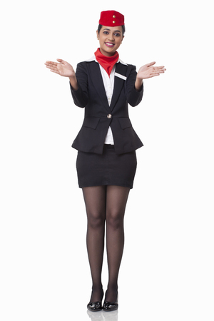 Portrait of young flight attendant gesturing over white background