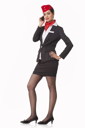 Full length portrait of a confident airhostess on call isolated over white background
