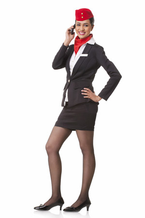 Full length portrait of young airhostess on call isolated over white background Stock Photo