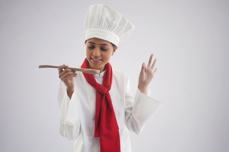Female chef tasting food isolated over gray background