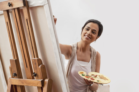 easel: Female artist painting on canvas isolated over gray background