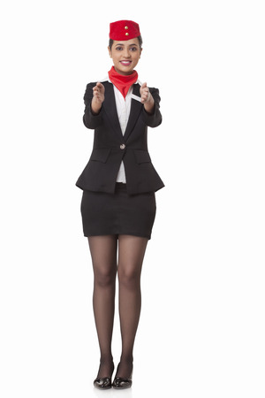 Flight attendant gesturing towards exits isolated over white background