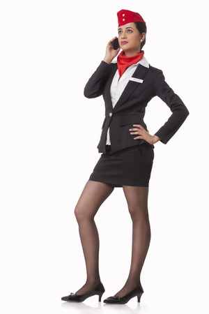 Full length of young airhostess using mobile phone while looking up over white background