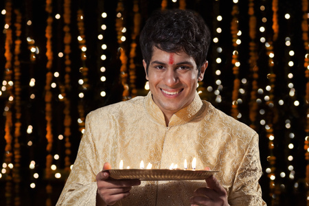 kurta: Portrait of a man holding a tray of diyas Stock Photo