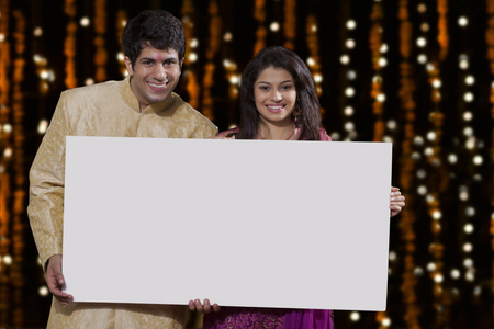 Portrait of couple holding a white board Stock Photo
