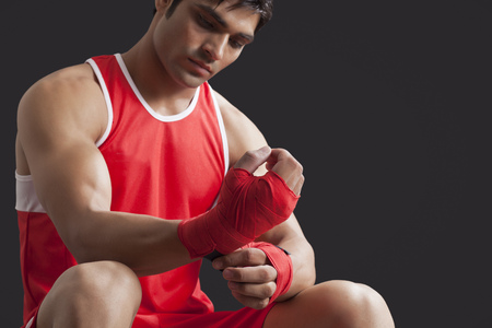 Confident male boxer taping up hands over black background