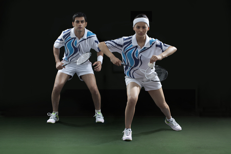 Portrait of man and woman playing badminton doubles at court Stock Photo