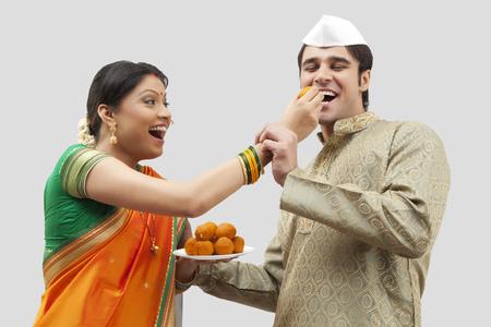 maharashtra: Maharashtrian woman feeding man a laddoo