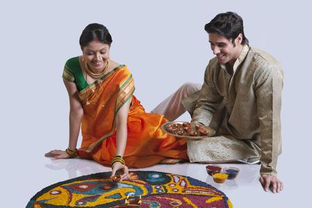 kurta: Maharashtrian couple placing diyas on rangoli