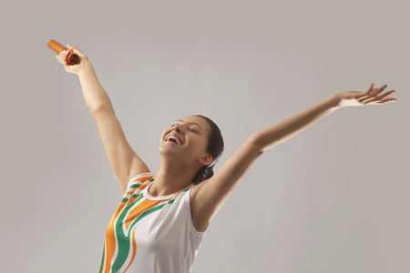 Jonge vrouwelijke estafetteloper het vieren overwinning die over grijze achtergrond wordt geïsoleerd