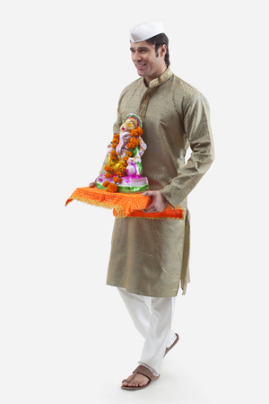 Maharashtrian man holding a Ganesh idol Stock Photo
