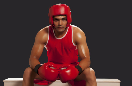 Young male Indian boxer sitting on bench isolated over black background
