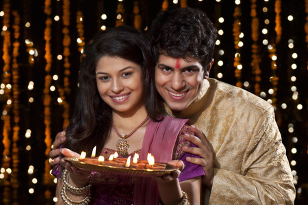 Portrait of a couple with a tray of diyas Stock Photo