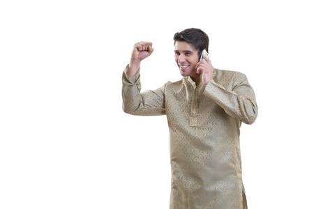 kurta: Bengali man cheering while talking on a mobile phone