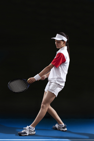Full length of female tennis player preparing to serve at court
