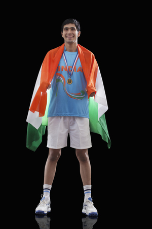 Happy Indian man in sportswear with Indian flag over black background