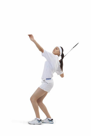 CHALLENGING: Woman in sports wear playing badminton against white background Stock Photo