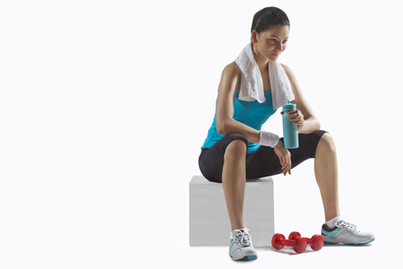 Fit young woman holding water bottle while lost in thoughts over white background