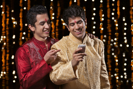 down lights: Men smiling at sms on mobile phone