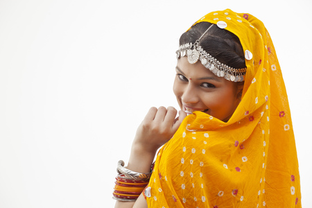 Portrait of shy woman in traditional clothing looking over shoulder against white background