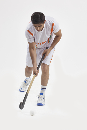 CHALLENGING: Young man playing field hockey isolated over white background