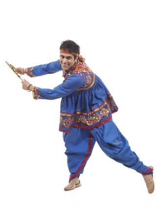 dhoti: Portrait of an Indian man performing Dandiya Raas over white background