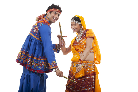 Portrait of happy couple performing Dandiya Raas against white background