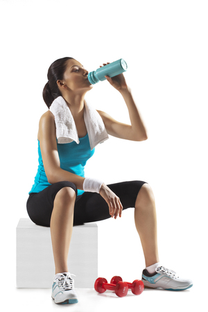 Young fit woman drinking water from bottle isolated over white background