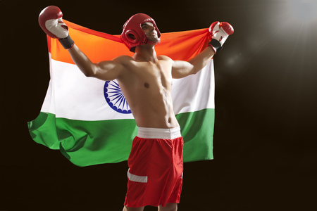 Successful male boxer looking up as he holds Indian flag isolated over black background
