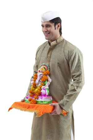 Maharashtrian man holding a Ganesh idol Stock Photo