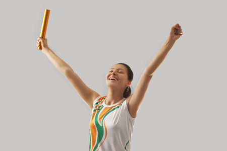 puños cerrados: Female relay runner celebrating victory against gray background